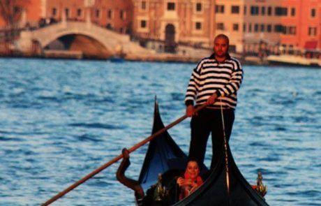 Gondolero navegando en canal de Venecia