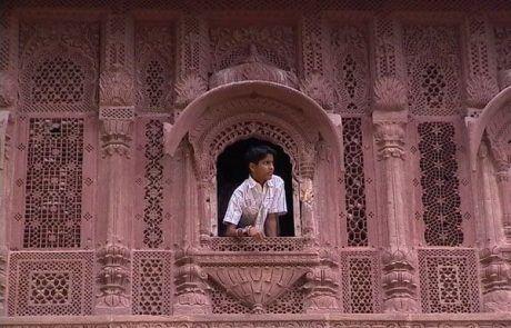 Niño mirando por una ventana del palacio de los vientos en Jaipur