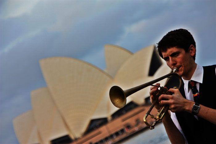 Hombre tocando trompeta con la Opera de fondo, Sidney