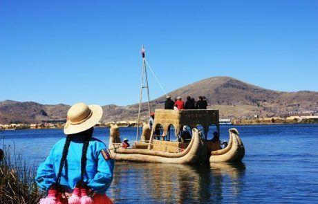 Mujer mirando barca en el lago Titicaca en Perú