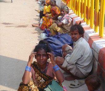 Multitud sentados en la sombra de una carretera en La India