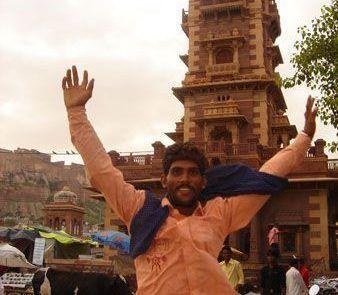 Retrato de un hombre frente a la torre del reloj en Jodhpur