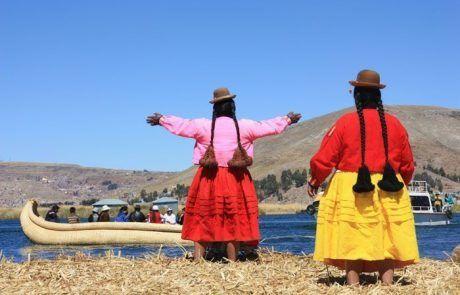 Mujeres avisando a barcos en las islas Uros en el lago Titicaca